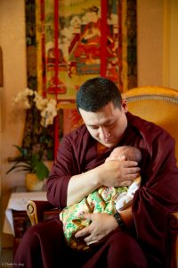 Thaye Dorje, His Holiness the 17th Gyalwa Karmapa, gently cradles his beloved son Thugsey