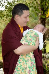 Thaye Dorje, His Holiness the 17th Gyalwa Karmapa, gently cradles his son Thugsey